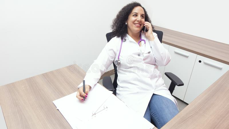 Female latin female doctor sitting smiling relax in her consulting room with stethoscope on her neck talking to her smart phone on. White background royalty free stock image