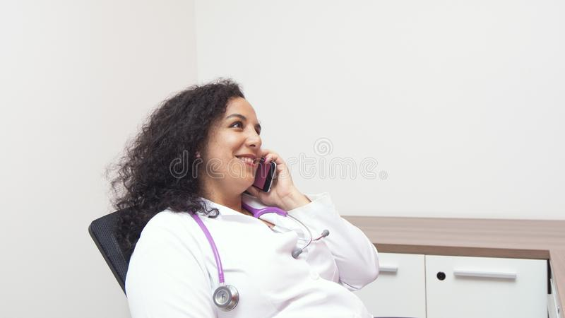 Female latin female doctor sitting smiling relax in her consulting room with stethoscope on her neck talking to her smart phone. On white background royalty free stock photography