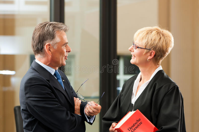 Female lawyer with civil law code and client. Female lawyer with German civil law code and client - only torsos to be seen, close-up royalty free stock images