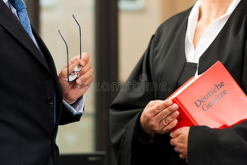 Female lawyer with civil law code and client. Female lawyer with German civil law code and client - only torsos to be seen, close-up stock photography