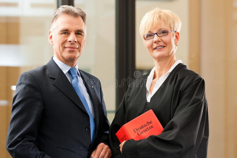 Female lawyer with civil law code and client. Female lawyer with German civil law code and client stock image
