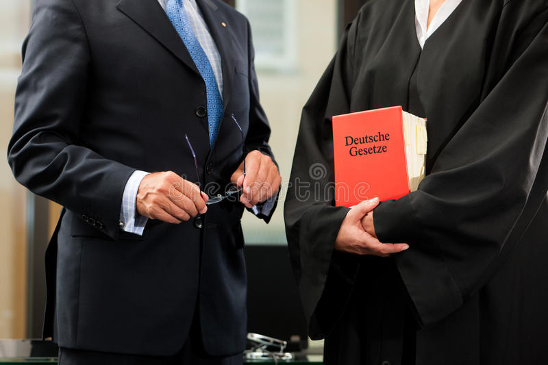 Female lawyer with civil law code and client. Female lawyer with German civil law code and client - only torsos to be seen, close-up stock photos