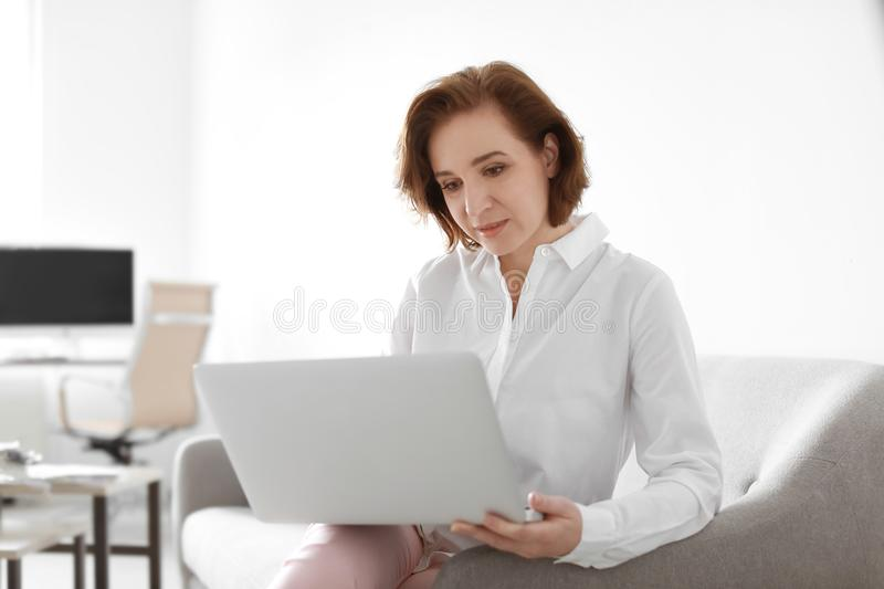 Female lawyer working with laptop. In office stock photography
