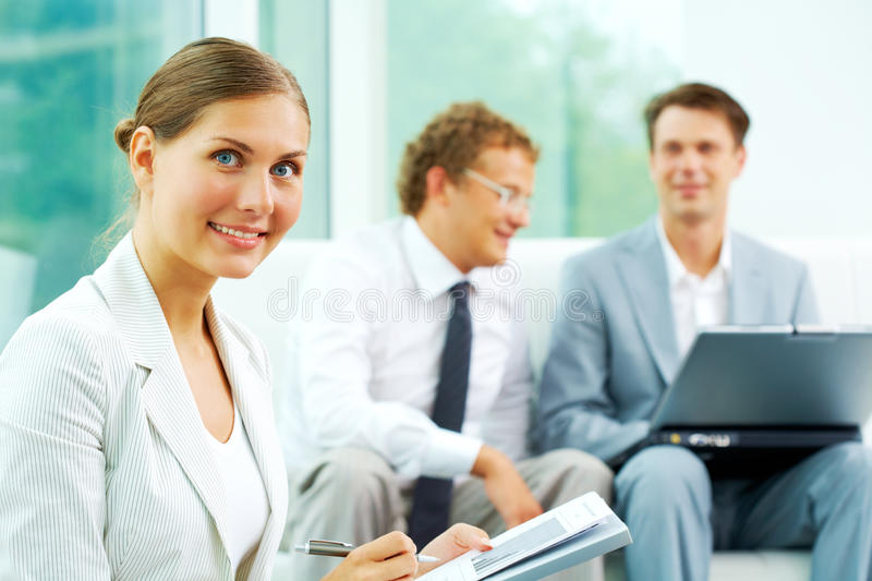 Female leader. Confident businesswoman looking at camera at background of communicating men stock photo