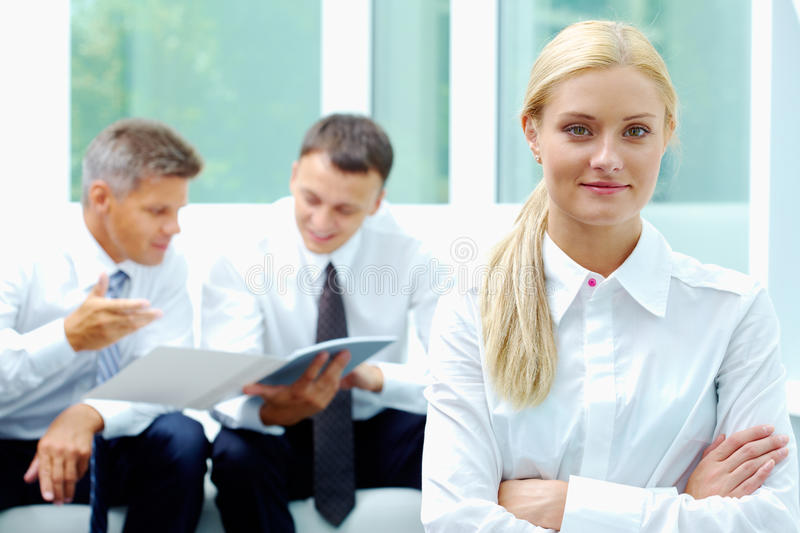 Female leader. Confident businesswoman looking at camera at background of communicating men stock photography