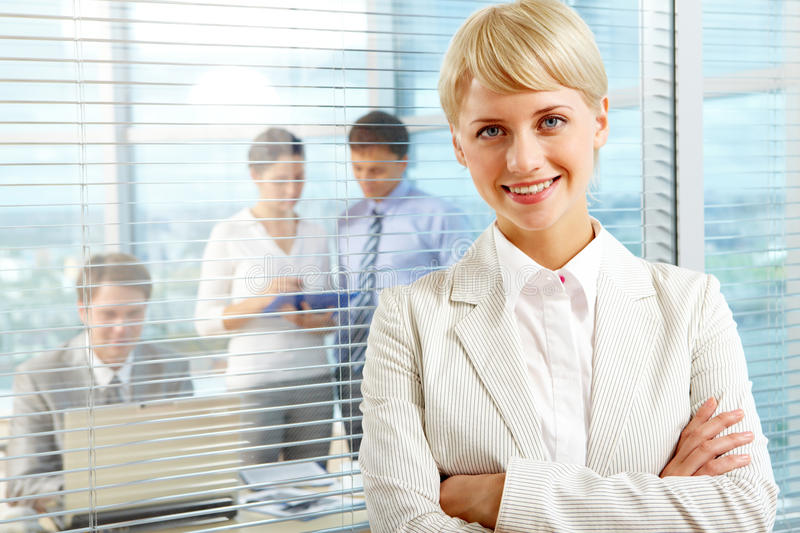 Female leader. Looking at camera with team of partners working in office behind royalty free stock image