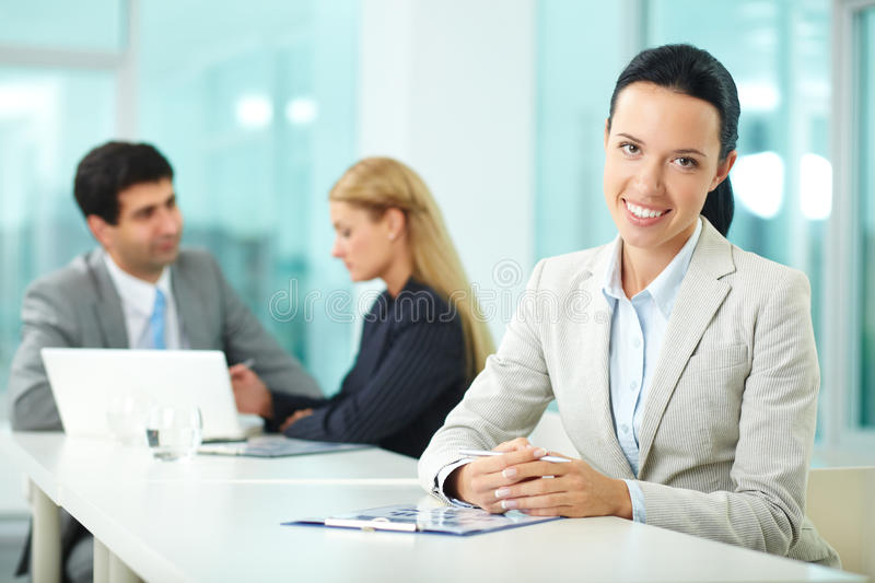 Female leader. Portrait of a young women at workplace looking at camera and smiling stock photography