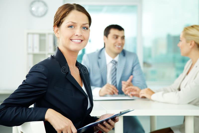 Female leader. A beautiful businesswoman looking at camera in working environment stock photo