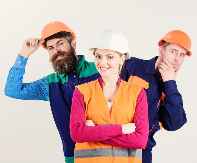 Female leader concept. Woman, leader in hard hat. With happy face stand in front of builders. Team of architects, builders, labourers peeking behind leader stock photo