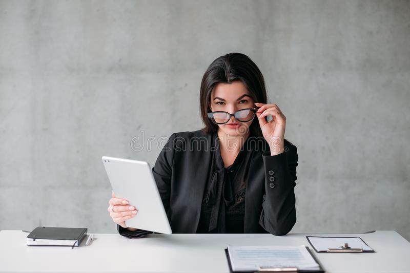 Female leader corporate lifestyle successful woman. Female leader. Corporate lifestyle. Successful business woman sitting at desk with tablet, taking off royalty free stock image