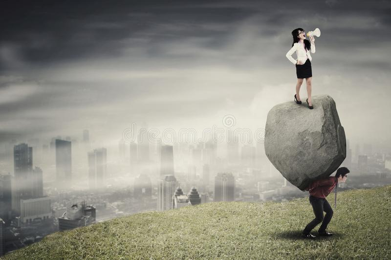 Female leader and his employee on the hill. Female leader standing on a stone while commanding his employee with a megaphone to climb on the hill stock photo