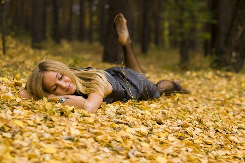 Female on leaves. Beautiful girl relaxing on yellow leaves