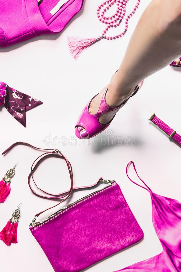 Female leg in sexy bright pink pumps hanging over white floor background with fashion outfit accessories: handbag, belt, churches. Jacket,silk top. Top view stock photography