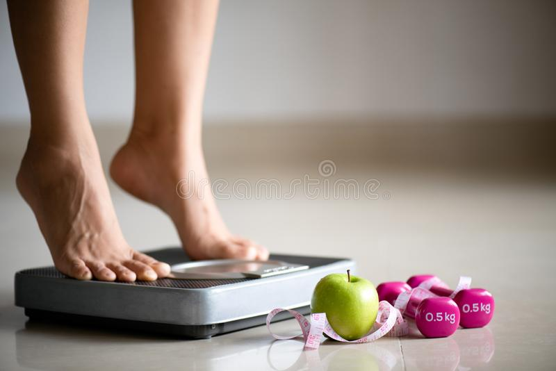 Female leg stepping on weigh scales with measuring tape, pink dumbbell and green apple. Healthy lifestyle, food and sport concept stock photos