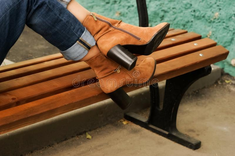 Female legs in autumn high heels boots in the street stock image