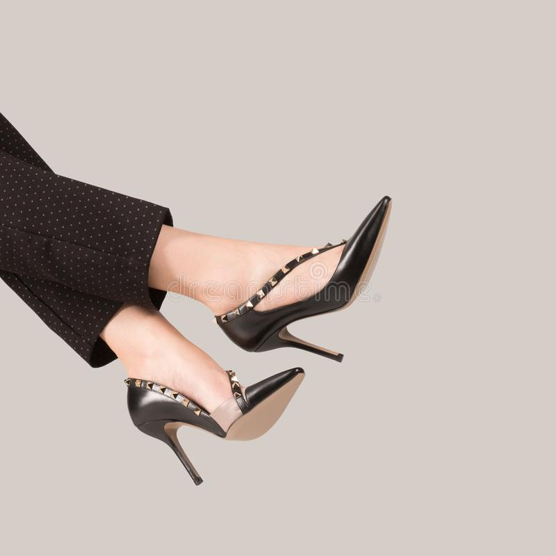 Female legs in beautiful expensive shoes with spikes royalty free stock image