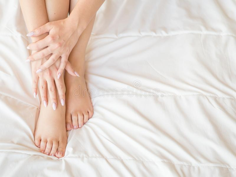 Female legs on bed. Cropped image of beautiful woman in bedroom. Horizontal photo, top view. Pedicure and skincare. Concept stock photos