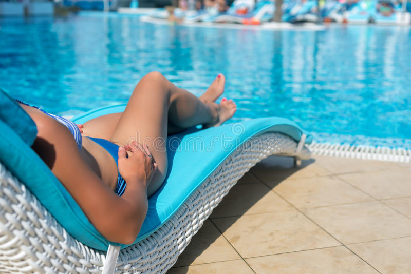 Female legs at blue water. Of swimming pool stock image