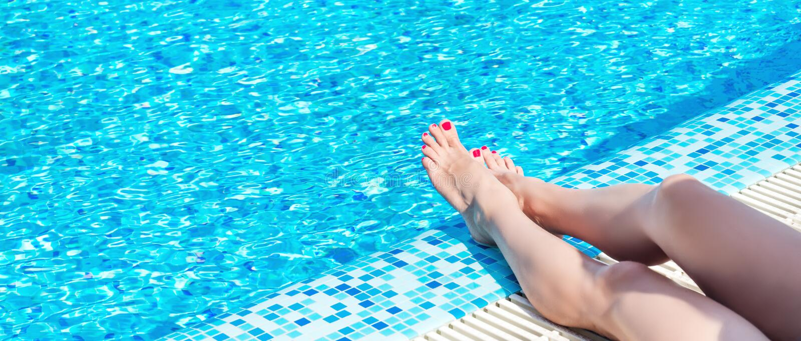 Female legs at blue water. Of swimming pool stock photos