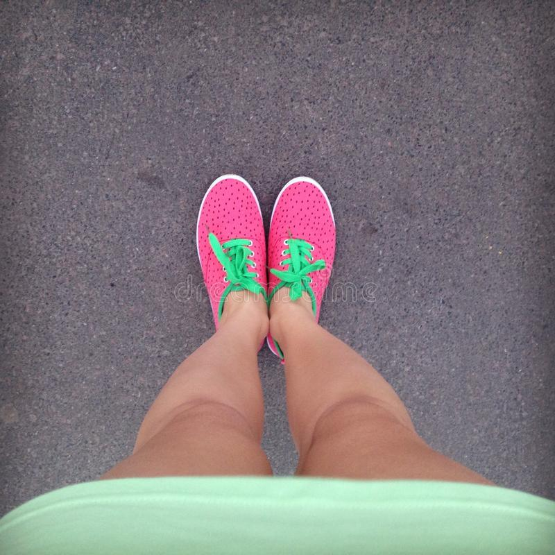 Female legs in bright pink sneakers with green laces on the asphalt. Green dress, sneakers in the form of strawberries. Top view. royalty free stock images