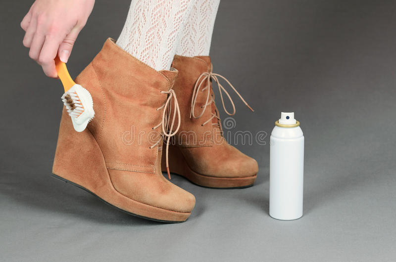 Female legs in brown suede boots on a gray background. Woman cleaning her suede shoes stock photo