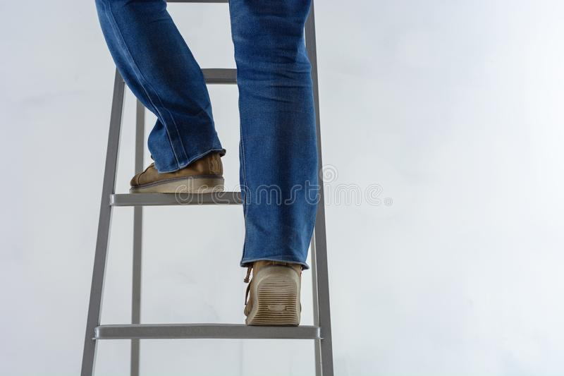 Female legs are climbing the stairs against the background of the white plastered wall. repair of premises royalty free stock images