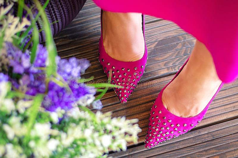 Female legs close-up. Pink shoes and dress on the summer terrace. Girl walks in the city outdoors. royalty free stock photo