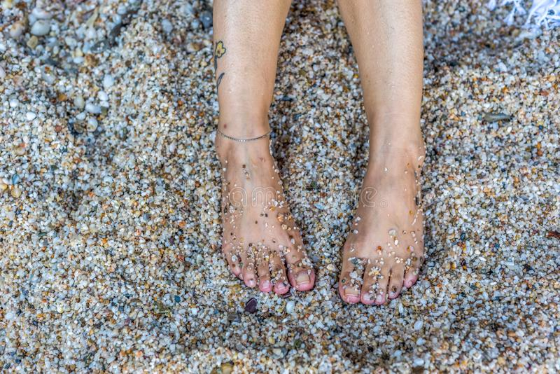 Female legs covered with pebbles on beach stock photo