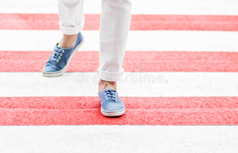 Female legs or feet crossing red crosswalk at summer day. Woman dressed in white jeans and blue loafers walking through stock photo