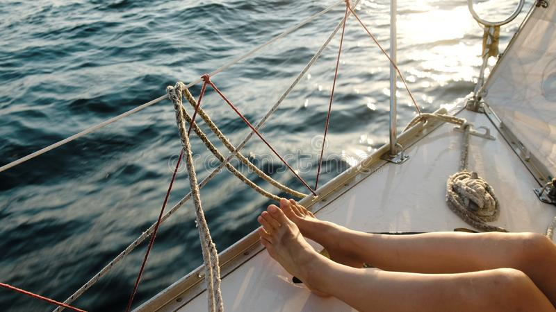 Female legs feet on the sailing yacht closeup in the open sea stock photos