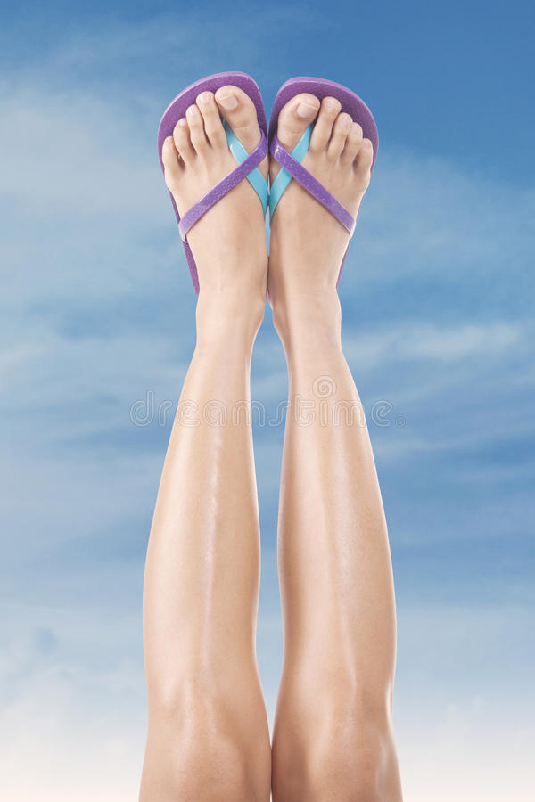 Female legs with flip-flops. Beautiful female legs with flip-flops upward. Shoot outdoors at summertime stock image