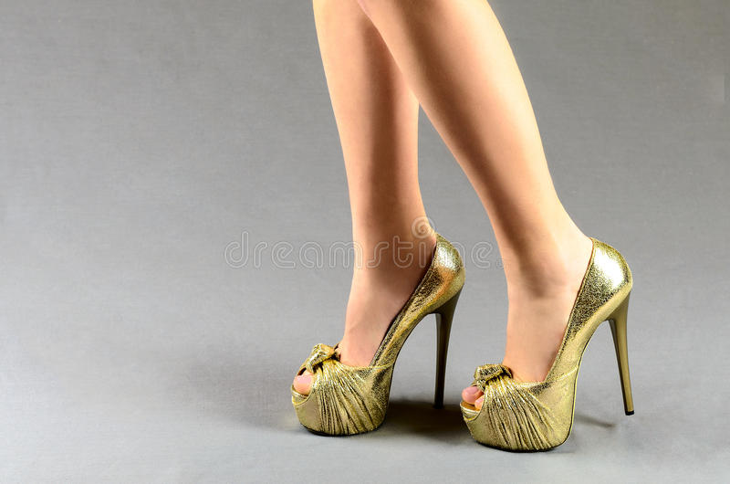 Female legs in gold shoes on a gray background royalty free stock image