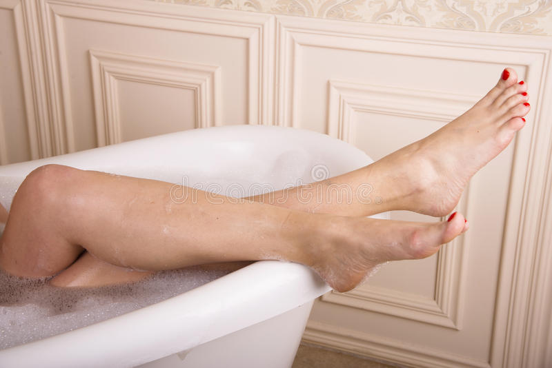 Female legs hang over the bathroom. stock image
