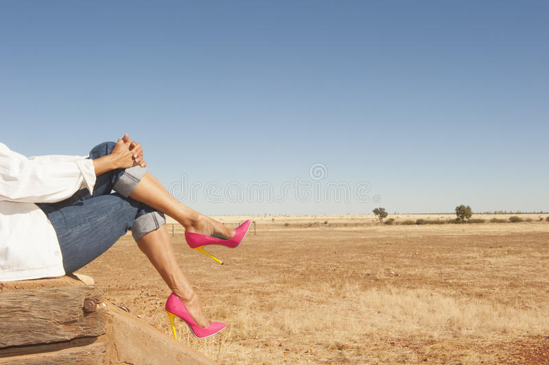 Female legs in high heel shoes sitting nature. Crosslegged female legs wearing colourful pink high heel shoes sitting relaxed outdoor, with field and blue sky as royalty free stock photo