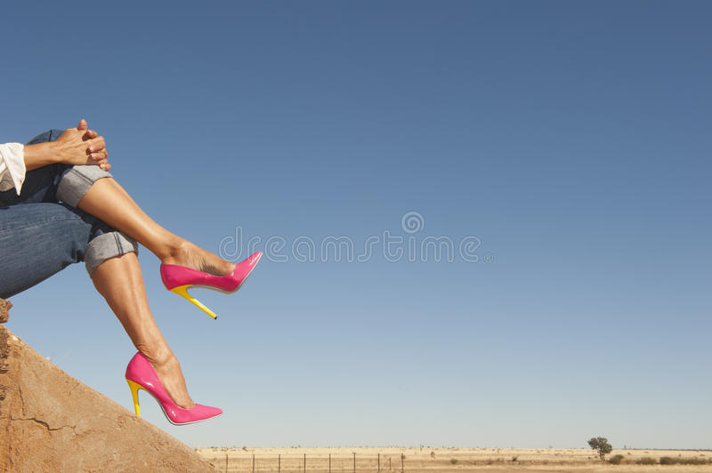 Female legs in high heel shoes sitting relaxed in nature. Attractive crosslegged Female legs wearing colourful pink high heel shoes sitting relaxed outdoor, with royalty free stock image