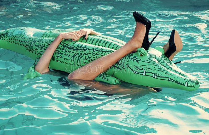 Female legs hold mattress in swimming pool. legs of girl embrace inflatable crocodile in pool water stock image