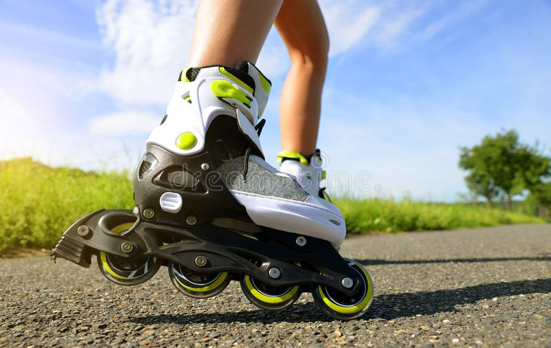 Female legs in inline skates. Female legs in inline skates in action outdoors on sunny day stock photography