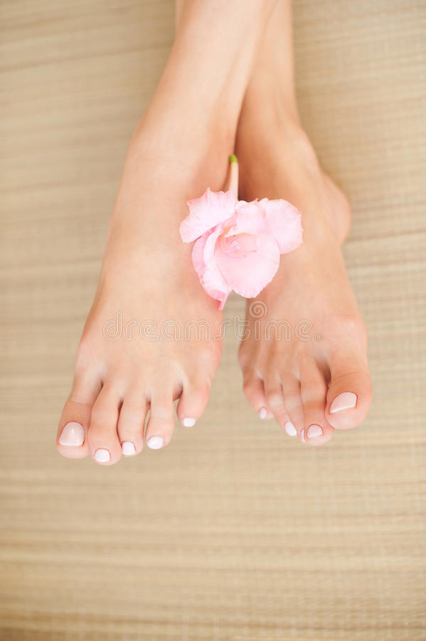 Female legs with light pink nails and flower stock images