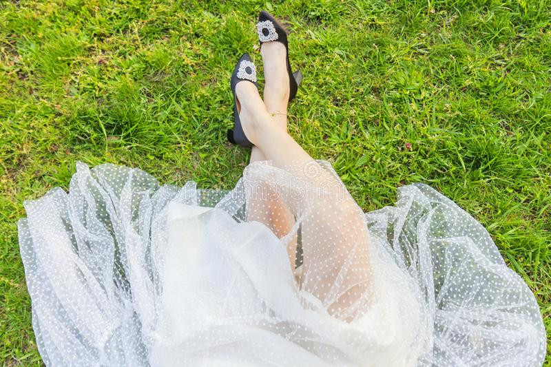 Female legs in new shoes and white skirt on green grass stock photo