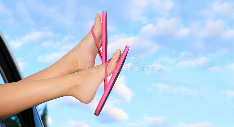 Female legs in pink sandals. Out from the car. Summer trip concept stock photos