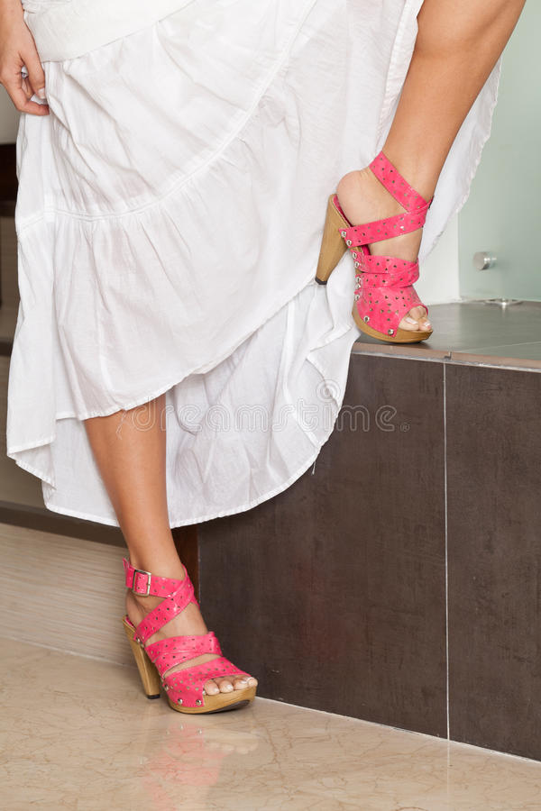Female legs with platform sandals color pink. Woman feet with pink sandals stock image