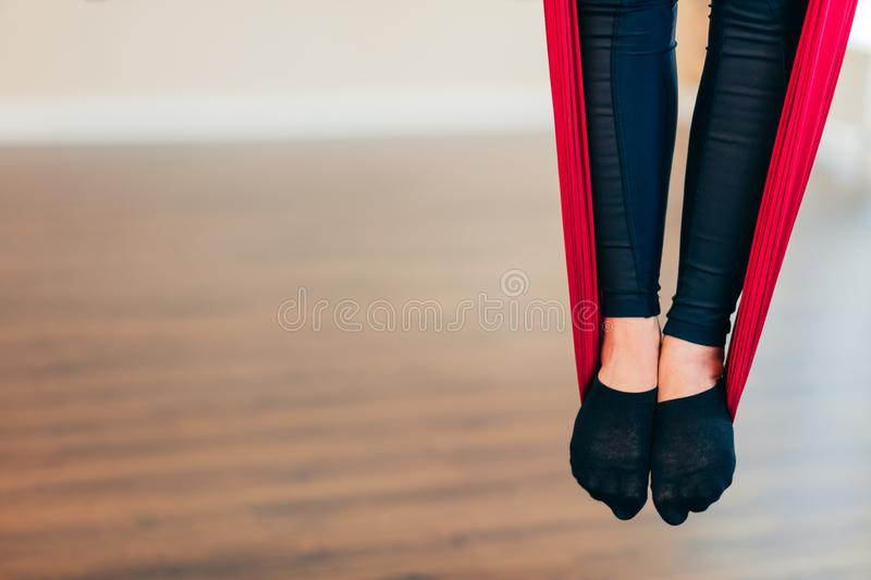 Female legs in red hammock on aerial yoga class, close up. royalty free stock images