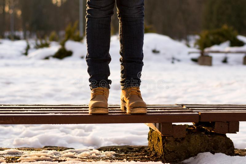 Female legs are standing on bench in winter sunny day. Blurred background of snow and sunset rays. Girk is walking in park. stock images