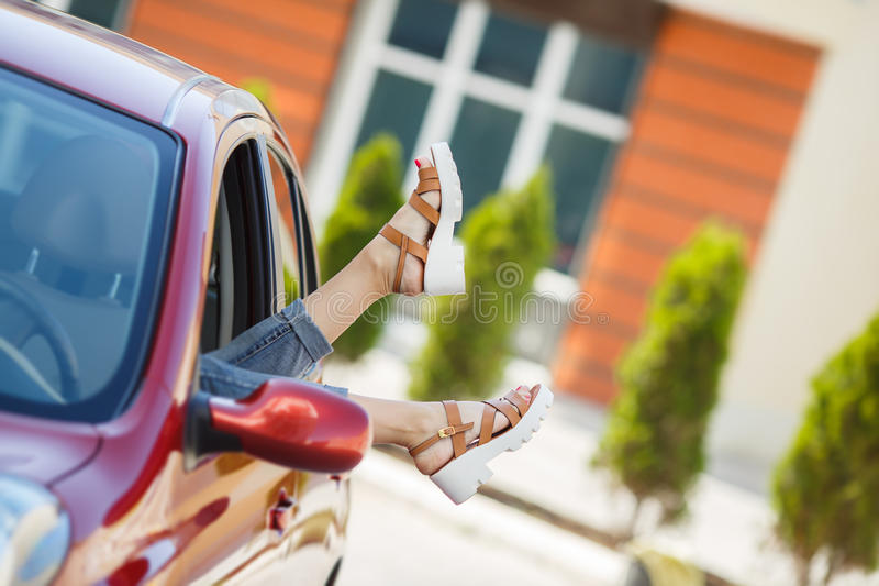 Female legs stick out of a car window. The young woman decided to rest on the side of the road in his small red car parked near the red house,sticking his feet stock image