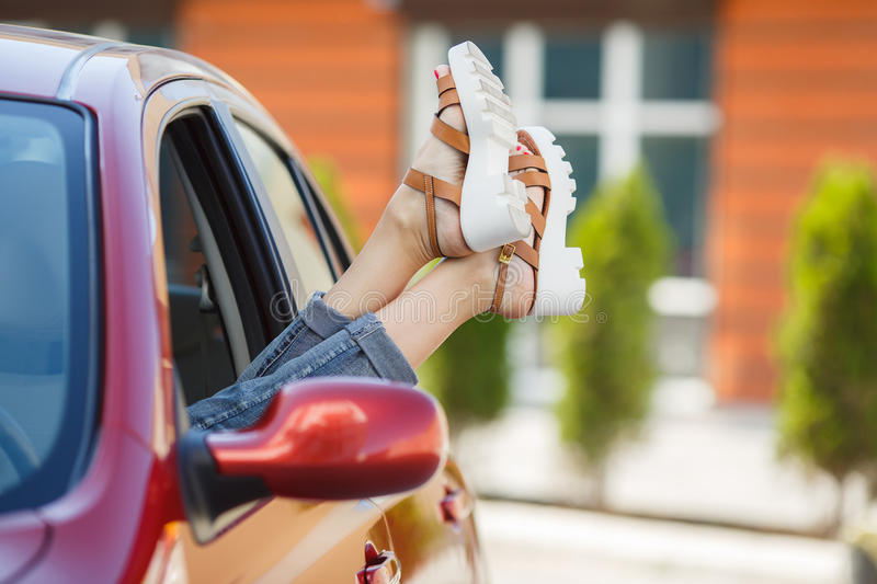 Female legs stick out of a car window. The young woman decided to rest on the side of the road in his small red car parked near the red house,sticking his feet stock photos