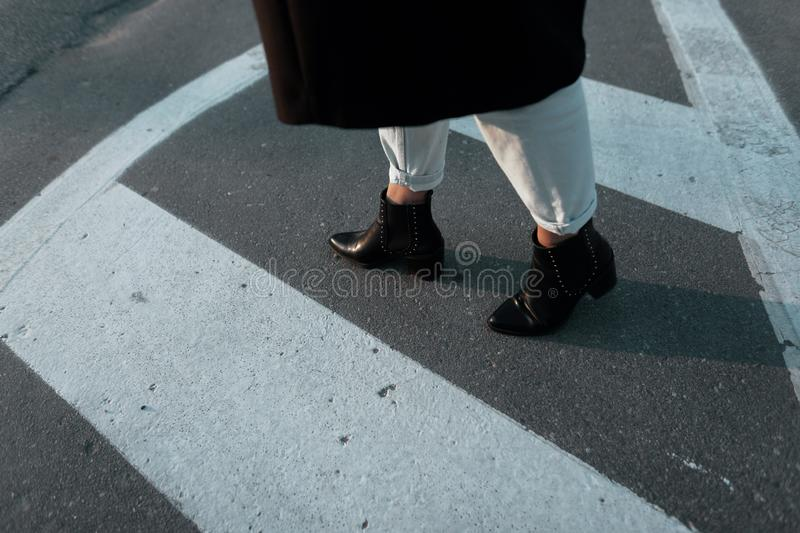 Female legs in stylish cropped jeans in vintage leather black heel shoes on a city street. Trendy elegant casual outfit. royalty free stock photo