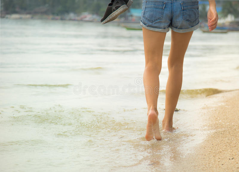 Female legs walking on water stock image