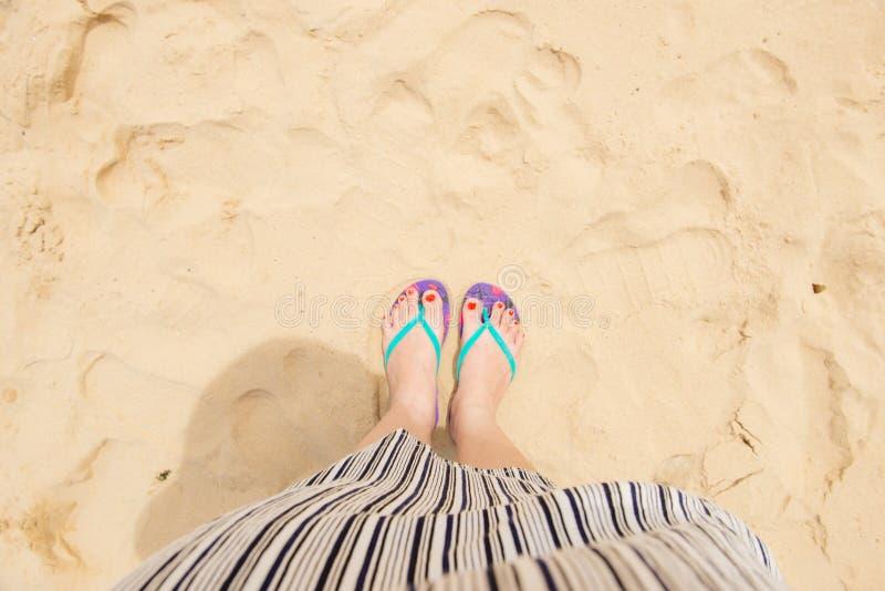 Female legs wearing flip flops near sea.  stock image