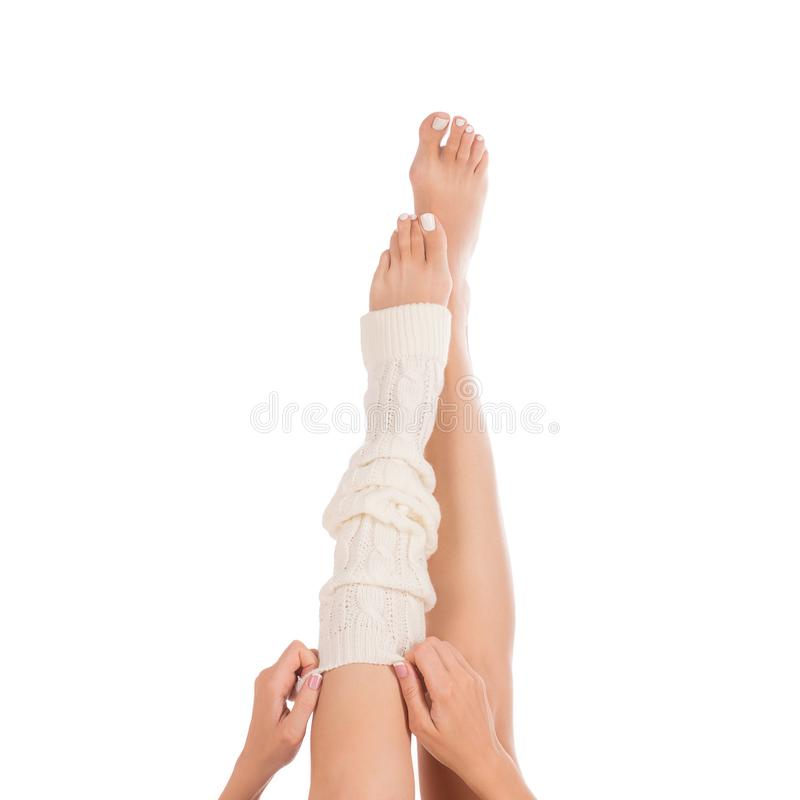 Female legs in white leg warmer. Female hands putting on a gaiter . White pedicure, french manicure. Close up, isolated royalty free stock images