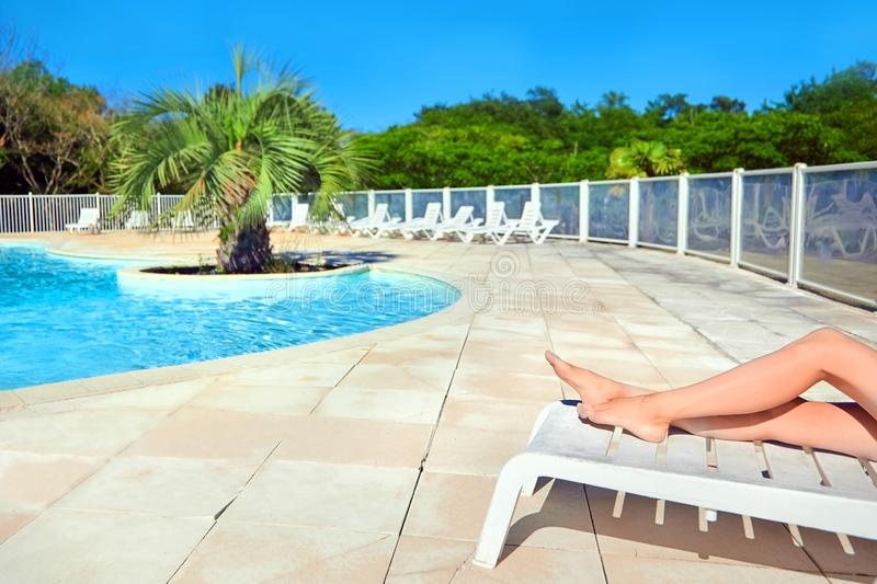 Female legs on a white sun lounger. Beautiful woman relaxing by the swimming pool with water royalty free stock image